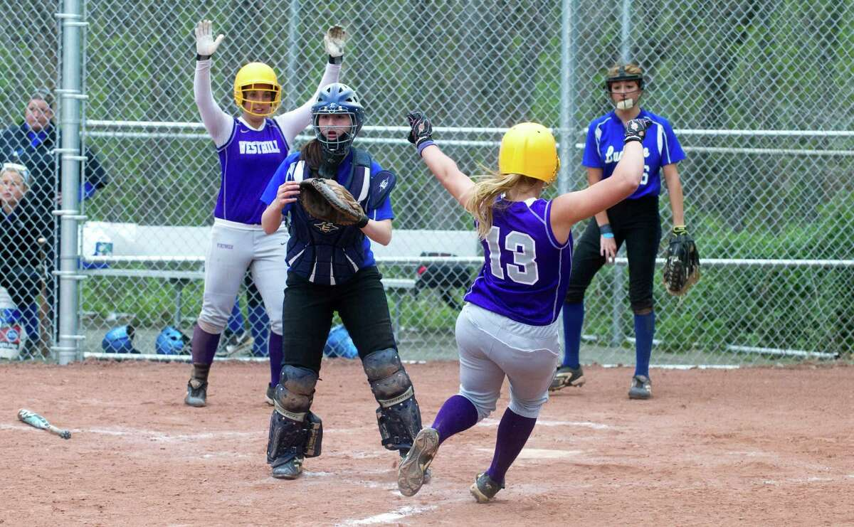 Westhill's Allison Macari slides home after hitting a home run as Ludlowe catcher Katie DeCarlo waits for the ball as Westhill High School hosts Ludlowe in a softball game in Stamford, Conn., April 18, 2012. Westhill's Cassandra Kish celebrates at left,