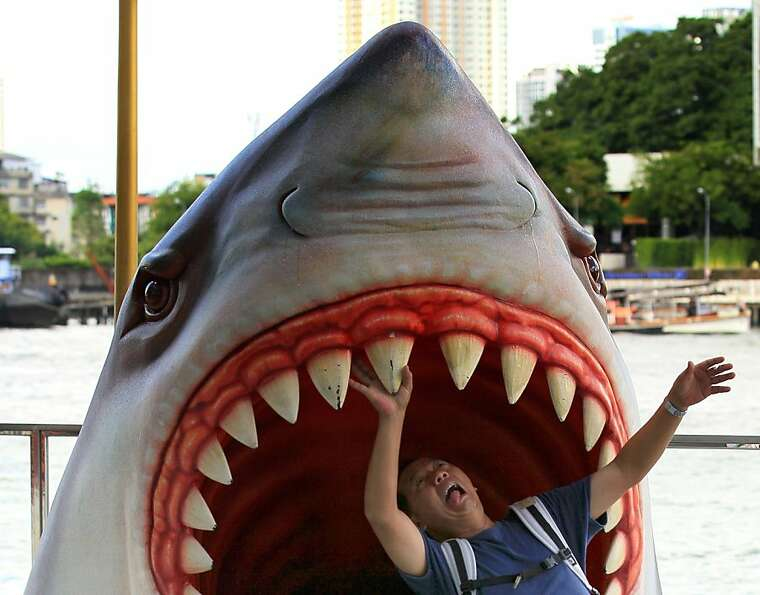 A tourist plays with a model of a giant shark in front of a shopping mall in Bangkok, Thailand Tuesd