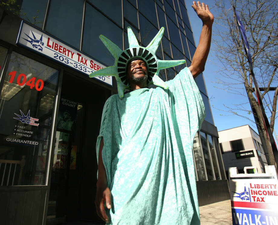 Dressed as Lady Liberty, Guy Diaz of Bridgeport greets passersby with a smile and a wave on the final day of tax filing season outside Liberty Tax Service at 100 Fairfield Avenue in Bridgeport on Tuesday, April 17, 2012. Photo: Brian A. Pounds / Connecticut Post
