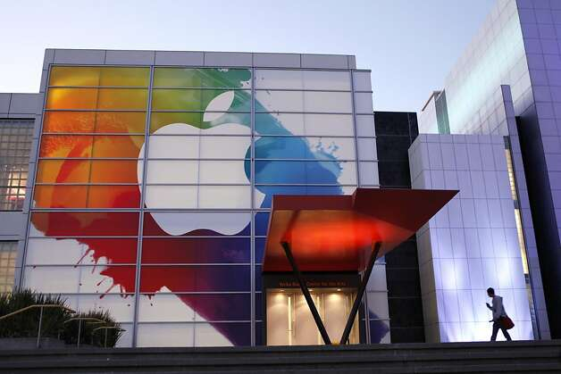 (FILES) An Apple logo is seen at the entrance of Yerba Buena Center for Arts in this March 6, 2012 file photo in San Francisco. Apple on March 19, 2012 said it plans to spend part of its cash hoard on paying a dividend to shareholders and buying back $10 billion in shares. Apple said it would pay a quarterly dividend of $2.65 per share from its huge cash balance, estimated to be at least $97 billion from sales of its hugely successful gadgets like the iPad and iPhone.  AFP Photo / Kimihiro Hoshino / FILES (Photo credit should read KIMIHIRO HOSHINO/AFP/Getty Images) Photo: Kimihiro Hoshino, AFP/Getty Images