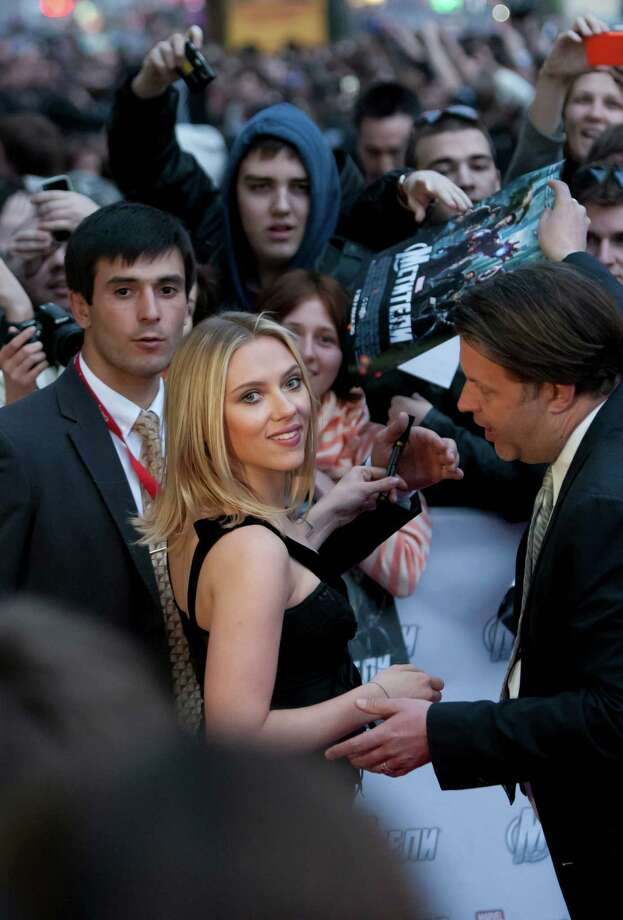 "Actress Scarlett Johansson smiles as she signs autographs while walking on the red carpet during the Russian premiere of the film ""Marvel"" in Moscow, Russia, Tuesday, April 17, 2012. (AP Photo/Alexander Zemlianichenko) Photo: Alexander Zemlianichenko / AP"