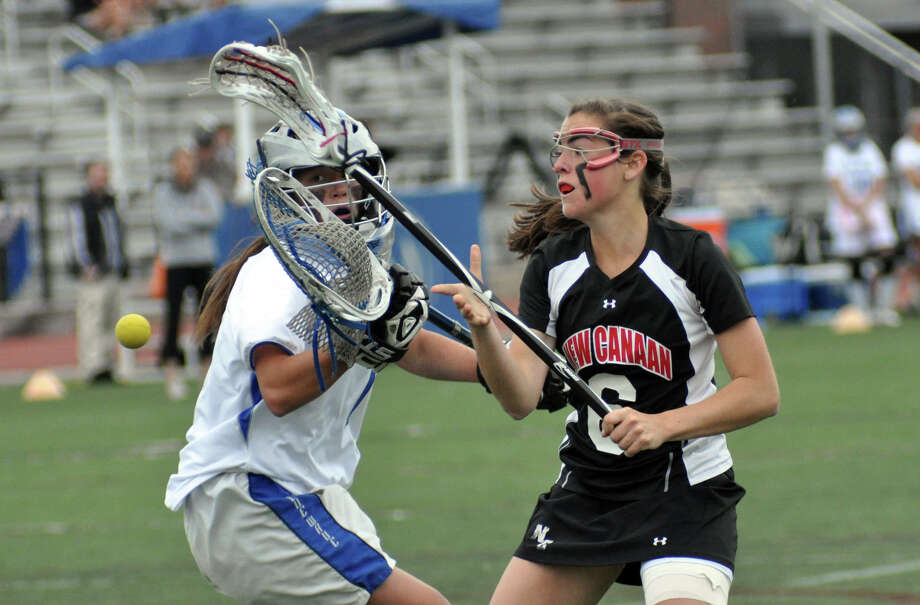 New Canaan's Beatrix Eppler (6) checks Darien's goalie Caylee Waters (1) knocking the ball loose during the girls lacrosse game at Darien High School on Wednesday, Apr. 18, 2012. Photo: Amy Mortensen