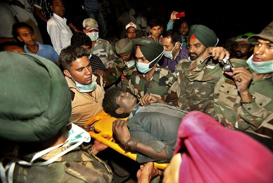 Rescue workers carry Indian survivor Sandeep out from the rubble of a factory that collapsed in Jalandhar, India, Wednesday, April 18, 2012. Rescue work continues at the site of a three-story blanket factory that collapsed in northern India close to midnight Sunday, killing at least five people. (AP Photo/Channi Anand) Photo: Channi Anand, Associated Press