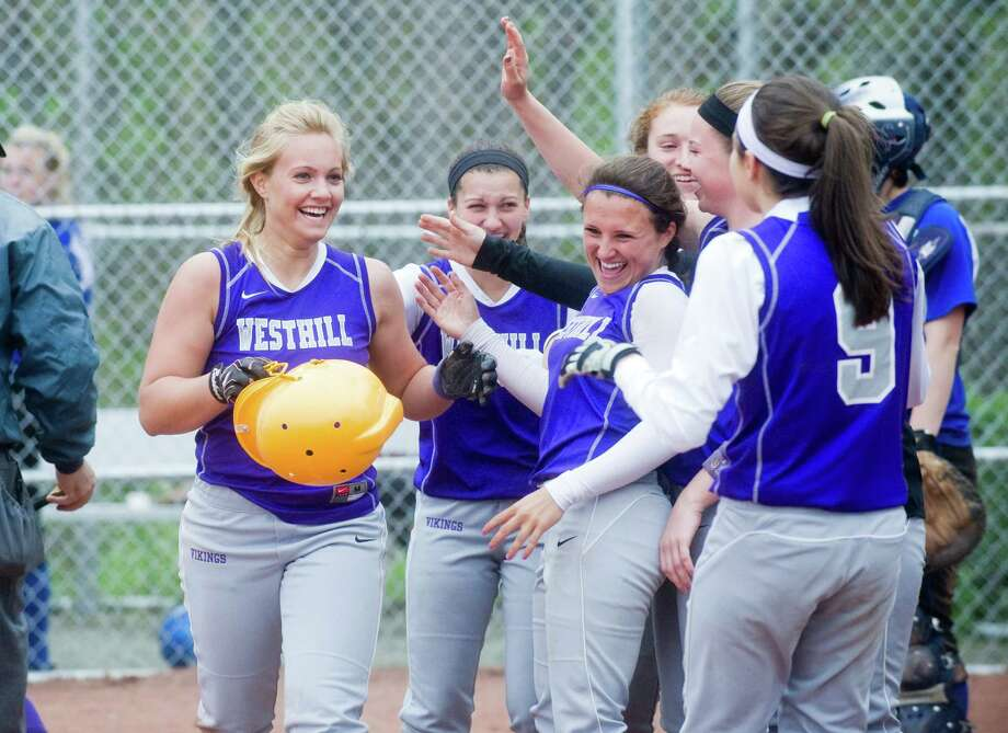 Westhill greets Allison Macari after she brought in a homer as Westhill High School hosts Ludlowe in a softball game in Stamford, Conn., April 18, 2012. Photo: Keelin Daly / Stamford Advocate