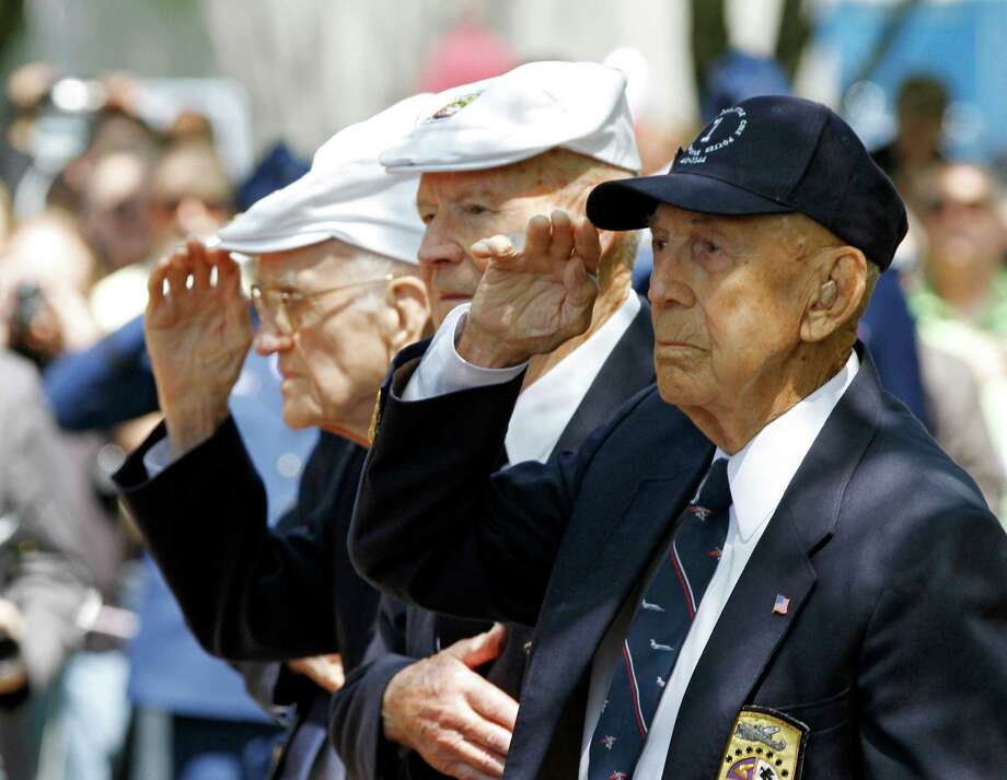 Surviving Doolittle Raider Richard E. Cole, right, salutes during the singing of the national anthem at a memorial service for the the 70th anniversary of the Doolittle raid on Tokyo at the National Museum of the United States Air Force in Dayton, Ohio Wednesday, April 18, 2012. Four survivors took part in the ceremonies including David Thatcher, second from right, Thomas C. Griffin, left, nd Edward E. Saylor, not seen. Photo: Mark Duncan, Associated Press / 2011 Assocated Press