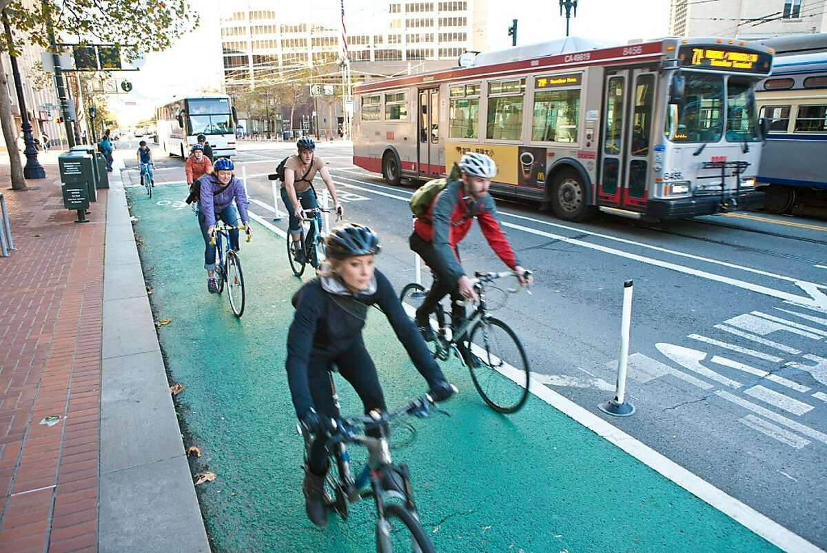 Bicyclists ride on a protected roadway on Market Street.
