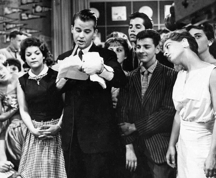 "Dick Clark is surrounded by fans in a 1957 telecast of ""American Bandstand."" As a television host, Clark helped bring rock 'n' roll into the mainstream. / AP1957"