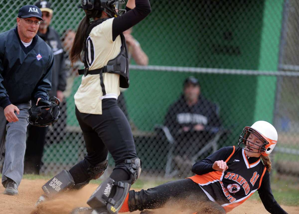 Stamford's Claire Kaptinski scores a run as Trumbull catcher Erica Quinones waits for the ball during their softball game Wednesday, April 18, 2012 at Trumbull High School.
