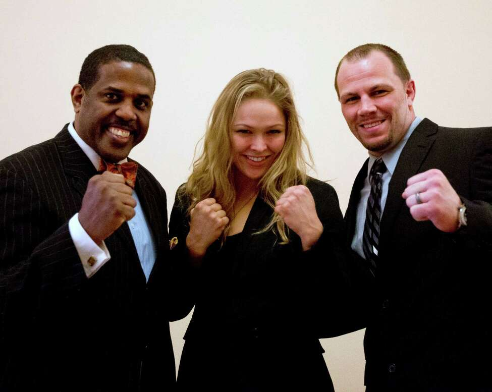 Sen. Kevin Parker, D-Brooklyn, left, poses with mixed martial arts athletes Ronda Rousey, center, and Nick Catone at the Capitol in Albany, N.Y., on Wednesday, April 18, 2012. The state Senate is expected to approve legislation again to make New York the 46th state to legalize and regulate the sport, though opposition remains in the state Assembly.