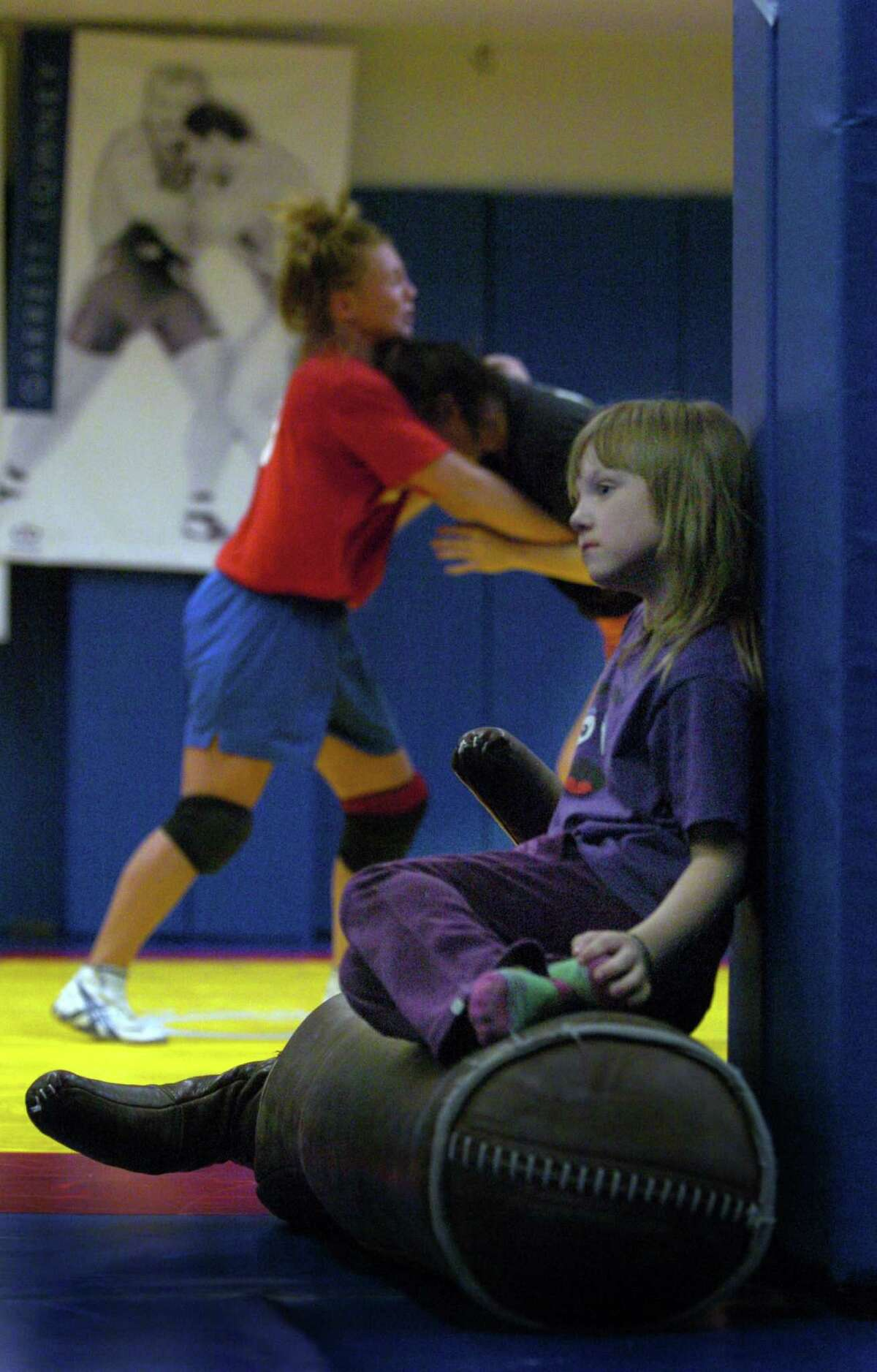 (DENVER, CO. 4/27/04) Kristie Marano, the only U.S. World Champion in 2003, is one of the most successful wrestlers of all time. She has been to 7 World Championships, and has won seven World Medals. She is also the mother of 6-year-old Kayla, born two weeks after Kristie won the University National and two weeks after her birth, Kristie won the U.S. Senior Nationals. Kayla watches her mother wrestling with fellow teammate Kaci Lyle, 22, from Eureka, California, during practice. (ROCKY MOUNTAIN NEWS PHOTO BY JUDY WALGREN)