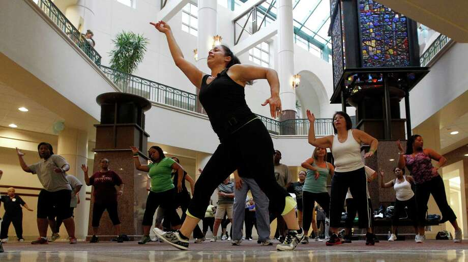 Zumba instructor Jessica Garcia leads an exercise class for Medical Center employees at Children's Memorial Hermann Hospital on Monday. Photo: James Nielsen / © 2012 Houston Chronicle
