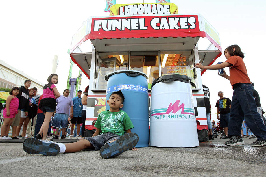 Elijah Jasso, 9, feels the effects of the Gravitron on the first day of the Fiesta Carnival at Lot C of the Alamodome. Recycling trash cans have been placed alongside regular trash cans at the carnival. Photo: Jerry Lara, San Antonio Express-News / © 2012 San Antonio Express-News