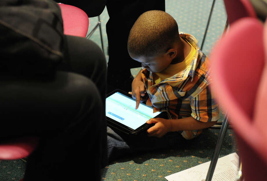 Jordan McKinley Allen, 4, who is a student at Honey Bear Learning Center and looks to be a quick study with his dad Mack's iPad, plays with it on the floor as Governor Dannel M. Malloy meets with Bridgeport families about his education reform proposals at the North Branch Library in Bridgeport, Conn. on Wednesday April 18, 2012. Photo: Christian Abraham / Connecticut Post