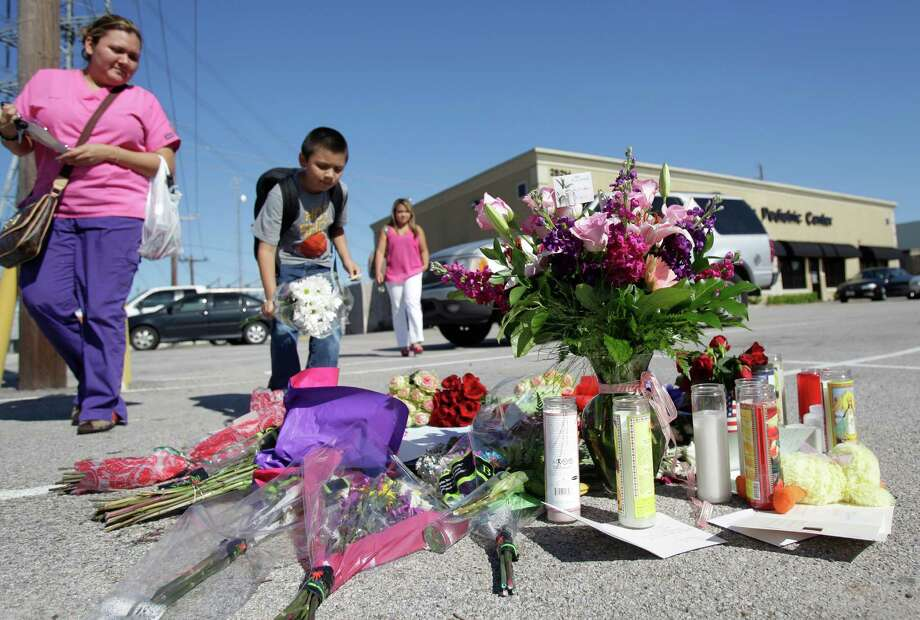 Araceli Canizales, left, with son Omar Canizales, 6, and Vannak Marroquin, visit a memorial for Kala Golden Schuchardt at the shooting scene in Spring. Schuchardt died trying to save her baby, who was later found unharmed. Photo: Melissa Phillip / © 2012 Houston Chronicle