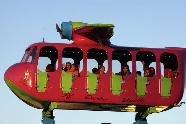 Children enjoy a ride on the first day of the Fiesta Carnival on Lot C of the Alamodome, Wednesday, April 18, 2012. This year, the carnival is getting greener with LED lights on some of the ride and recycling trash cans alongside regular trash cans. Photo: JERRY LARA, San Antonio Express-News / © 2012 San Antonio Express-News