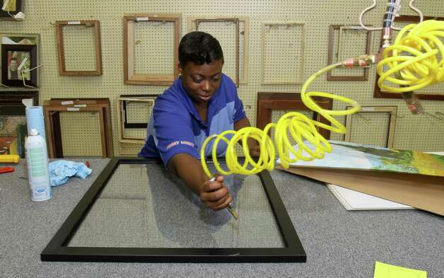 Rachel Dixon prepares a frame in the Hobby Lobby framing department. Photo: Gary Fountain / Copyright 2012 Gary Fountain.