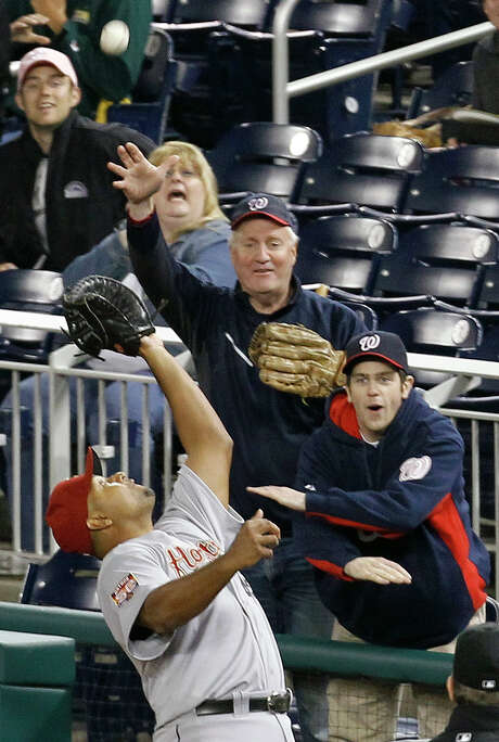Astros first baseman Carlos Lee ignores the fans and catches a foul ball hit by the Nationals' Ian Desmond. Photo: Ann Heisenfelt / FR13069 AP