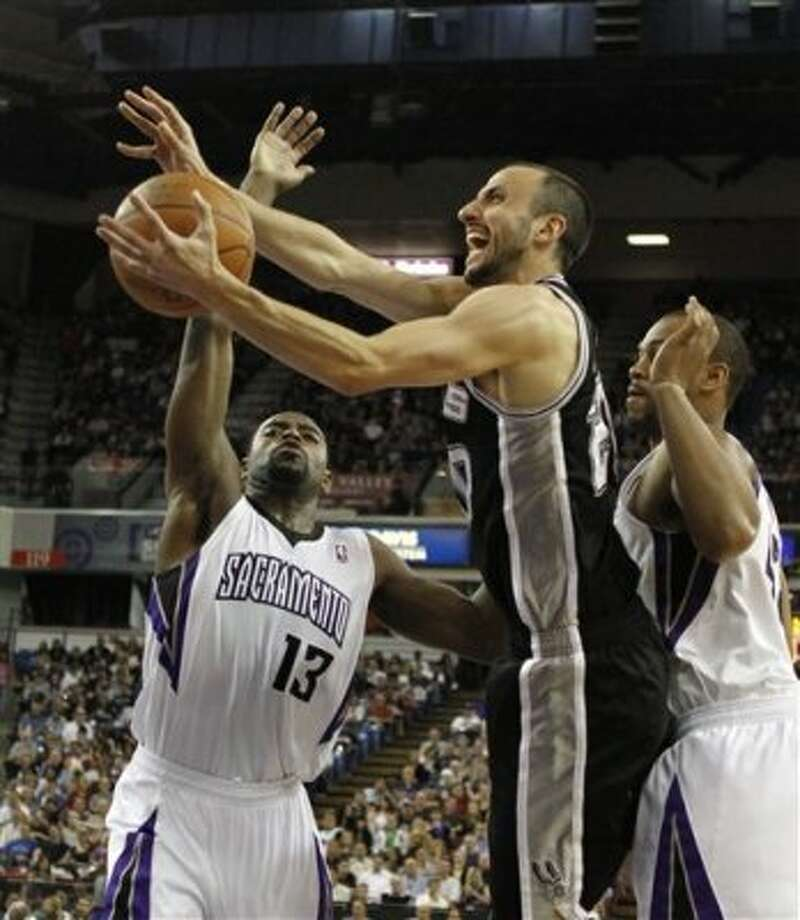 San Antonio Spurs forward Manu Ginobili, center, of Argentina, drives to the basket between Sacramento Kings' Tyreke Evans, left, and Chuck Hayes during the first quarter of an NBA basketball game in Sacramento, Calif., Wednesday, April 18, 2012. (AP Photo/Rich Pedroncelli) (AP)