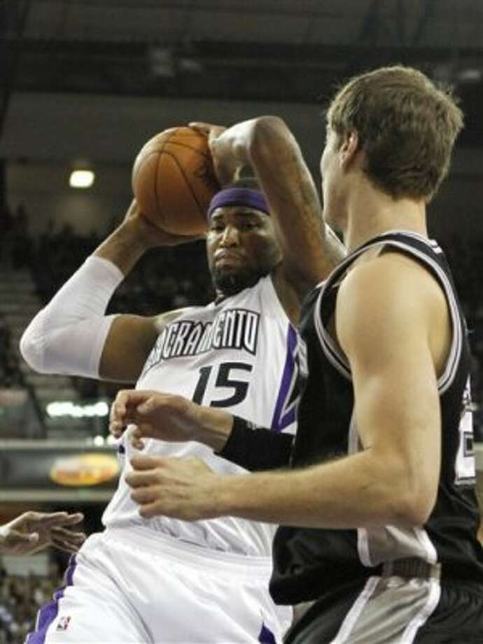 Sacramento Kings center DeMarcus Cousins, left, pulls a rebound away from San Antonio spurs center Tiago Splitter, of Brazil during the first quarter of an NBA basketball game in Sacramento, Calif., Wednesday, April 18, 2012. (AP Photo/Rich Pedroncelli) (AP)