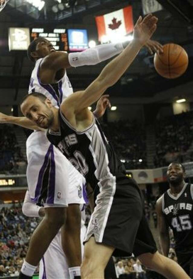 Sacramento Kings forward Jason Thompson, left, goes for the ball after San Antonio Spurs forward Manu Ginobili, right, of Argentina, was  fouled by Kings center DeMarcus Cousins (not shown) during the first quarter of an NBA basketball game in Sacramento, Calif., Wednesday, April 18, 2012. (AP Photo/Rich Pedroncelli) (AP)
