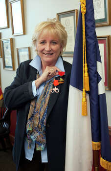 District Attorney Susan Reed shows-off the two Fiesta medals she will be giving away this year, in her office, Wednesday, April 11, 2012. Photo: J. Michael Short , For The Express-News / THE SAN ANTONIO EXPRESS-NEWS
