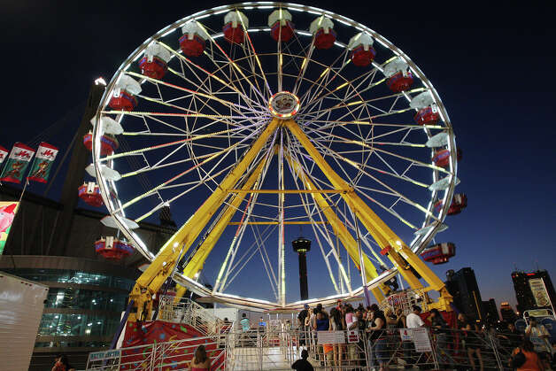 People line up to board the 100-foot Giant Wheel on the first day of the Fiesta Carnival by the Alamodome, Wednesday, April 18, 2012. This year, the carnival is getting greener with LED lights on some of the ride and recycling trash cans alongside regular trash cans. With the change to LED lights, the amp usage for the Giant Wheel went from 400 to 37 amps, said Wade Shows President Frank Zaitshik. Photo: JERRY LARA, San Antonio Express-News / © 2012 San Antonio Express-News