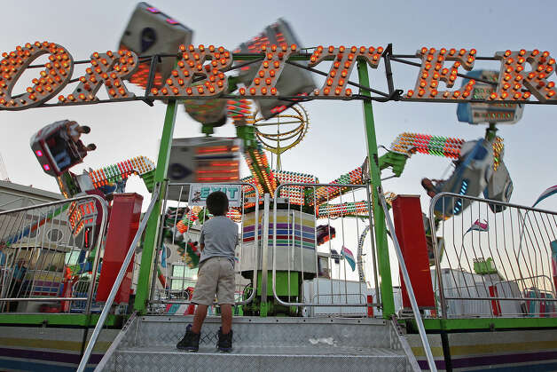 Too small to ride, Jared Sandoval, 5, watches his cousins ride the Orbitor on the first day of the Fiesta Carnival at the Alamodome, Wednesday, April 18, 2012. This year, the carnival is getting greener with LED lights on some of the ride and recycling trash cans alongside regular trash cans. Photo: JERRY LARA, San Antonio Express-News / © 2012 San Antonio Express-News
