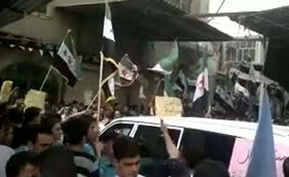 An image grab taken from a video uploaded on youtube on April 18, 2012, allegedly shows anti-regime protesters, waving the pre-Baath former national flag adopted by the Syrian opposition, surrounding the car of a team of UN observers during their tour the same day in the Damascus suburb of Irbin. Anti-regime protesters took to the streets in the outer suburb of the Syrian capital as the UN team overseeing a shaky truce toured the area, according to an amateur video posted online. Photo: -, AFP/Getty Images