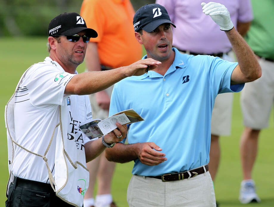 Matt Kuchar measures a fairway shot with his caddy as he plays the 18th hole during the Oak Farms Dairy Pro-Am  at the TPC Oaks Course on  April 18, 2012.  Tom Reel/ San Antonio EXpress-News Photo: TOM REEL, Express-News / San Antonio Express-News