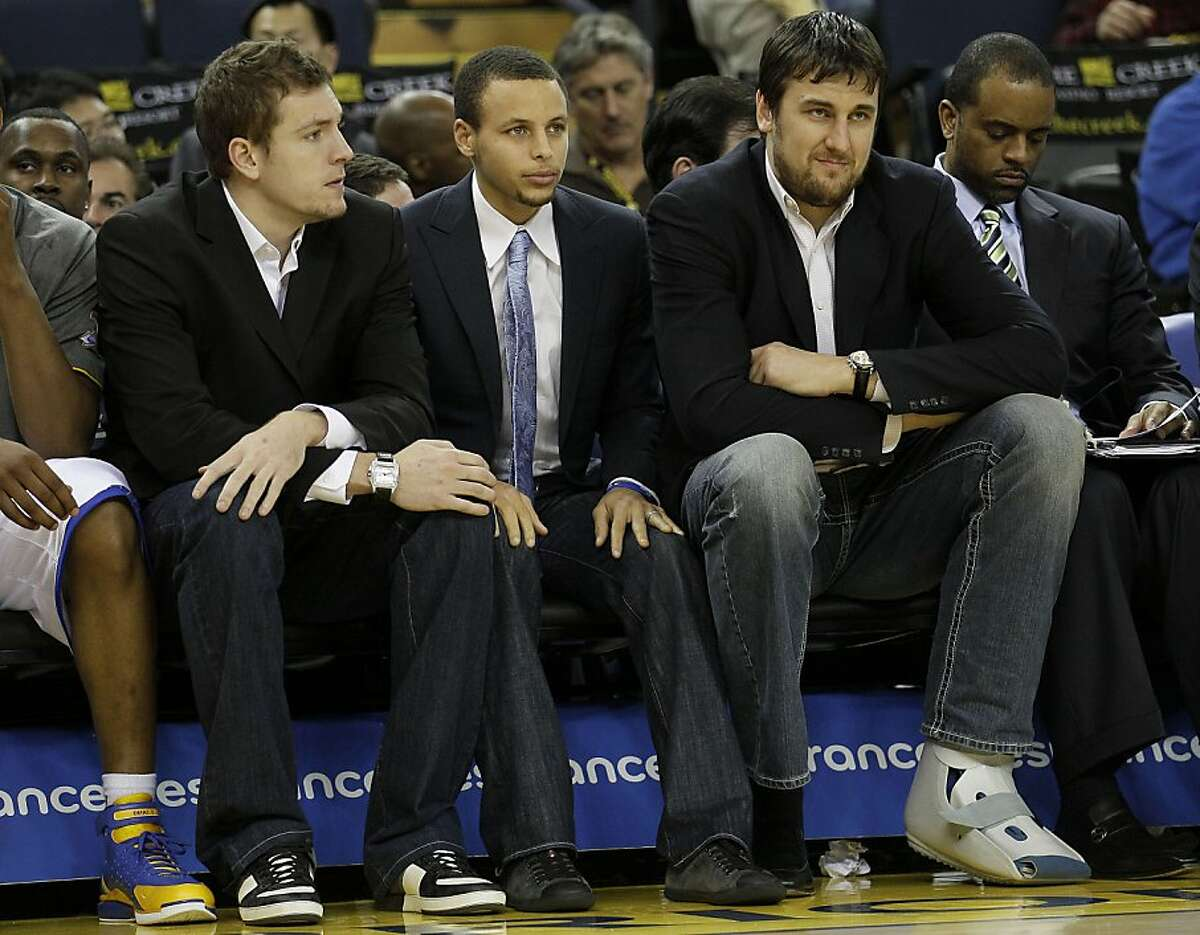 Injured Golden State Warriors players David Lee, from left, Stephen Curry, and Andrew Bogut, from Australia, sit on the bench during the third quarter of an NBA basketball game against the San Antonio Spurs in Oakland, Calif., Monday, April 16, 2012. (AP Photo/Jeff Chiu)