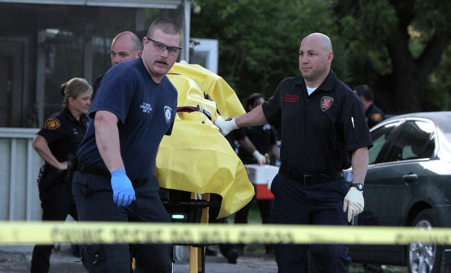 San Antonio Fire Department paramedics remove a female victim from an apparent attack that took place early Thursday at 4534 Emil street on the city's East Side. Photo: John Davenport/San Antonio Express-News