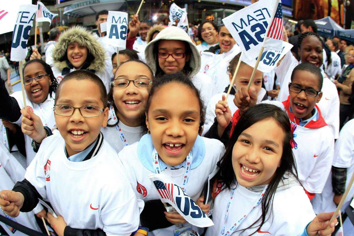 NEW YORK, NY - APRIL 18: Young fans cheer and show support for the Olympic hopefuls during the Team USA Road to London 100 Days Out Celebration in Times Square on April 18, 2012 in New York City.