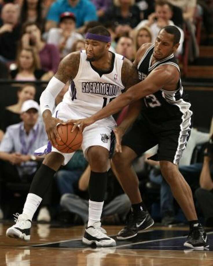 San Antonio Spurs center Boris Diaw, right, of France, hits the ball out of the hand of Sacramento Kings center DeMarcus Cousins during the first quarter of an NBA basketball game in Sacramento, Calif., Wednesday, April 18, 2012. (AP Photo/Rich Pedroncelli) (AP)
