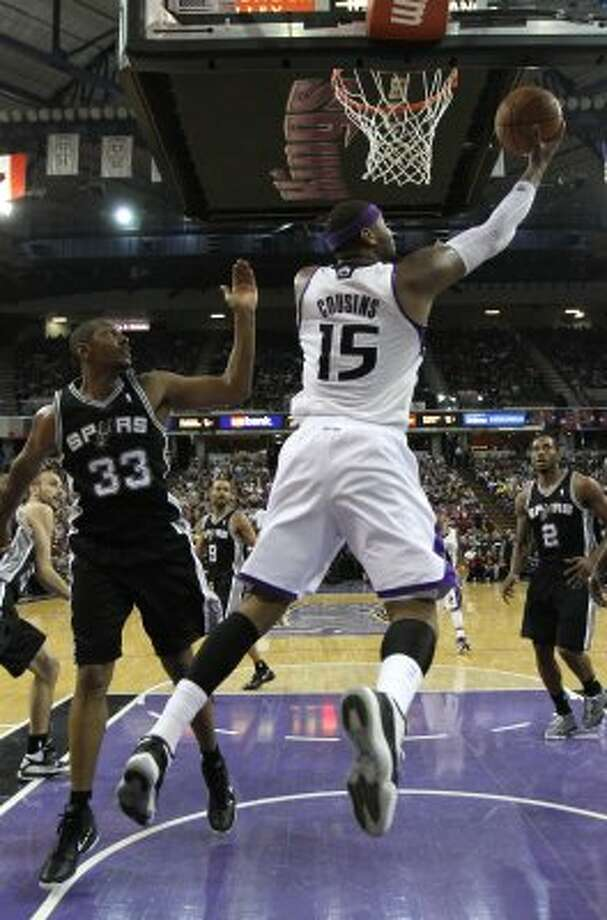 Sacramento Kings center DeMarcus Cousins, right, does a reverse layup past San Antonio Spurs center Boris Diaw, of France, left, during the second half of an NBA basketball game in Sacramento, Calif., Wednesday, April 18, 2012.  The Spurs won 127-102.(AP Photo/Rich Pedroncelli) (AP)