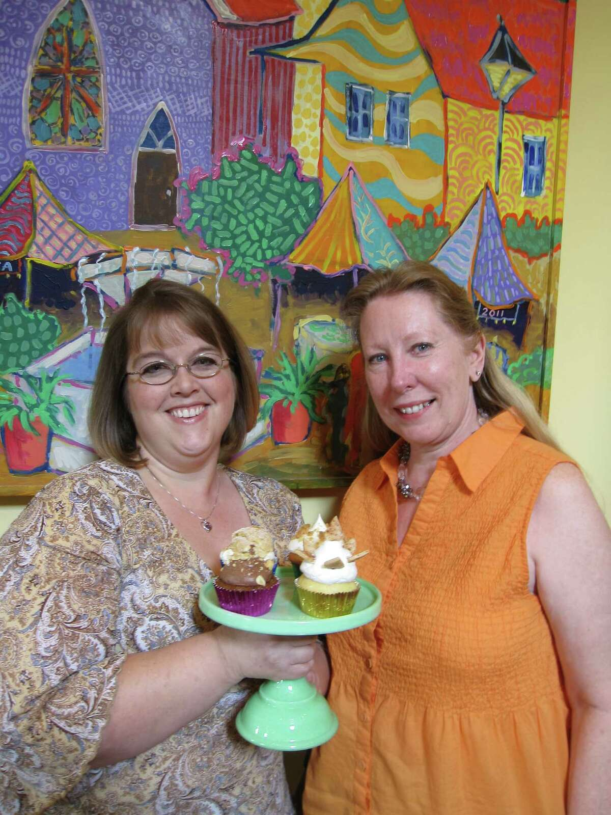 Kimberly Scandrett (left), a pastry chef and owner of Scratch Bakery, designed four gourmet cupcakes for NIOSA. NIOSA chairman Kathy Dewaal.