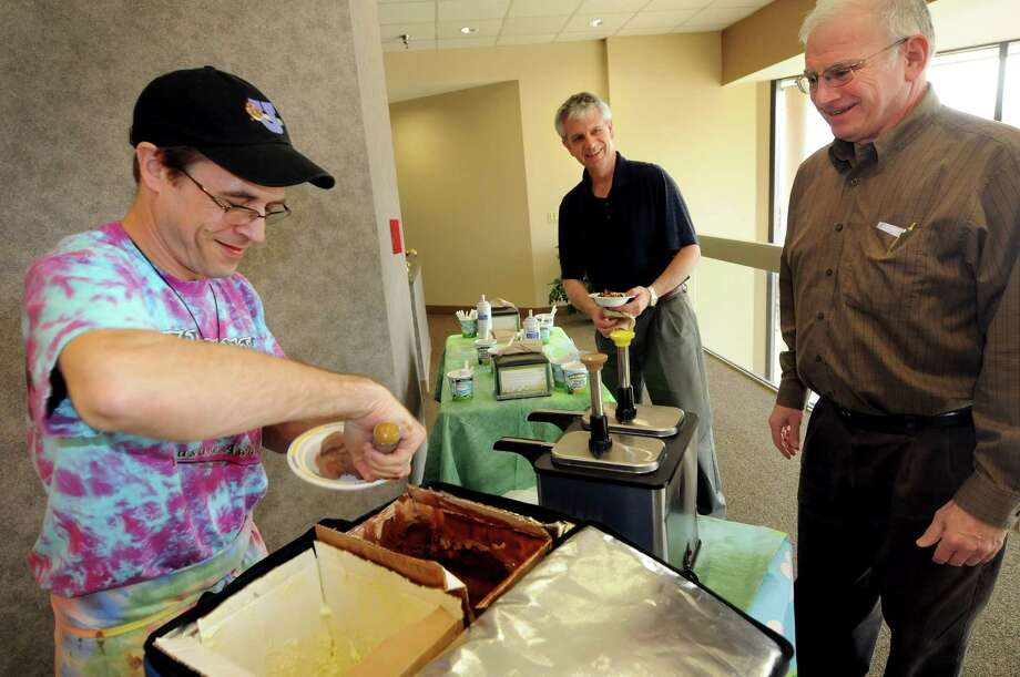 Rich Wilson of Ben & Jerry's, left, serves frozen treats to CPA Leslie Samiof, right, and firm partner Steve Cardinal to celebrate the end of corporate tax season on Thursday, March 15, 2012, at Teal, Becker & Chiaramonte in Albany, N.Y. The firm was voted a top place to work. (Cindy Schultz / Times Union) Photo: Cindy Schultz / 00016771A