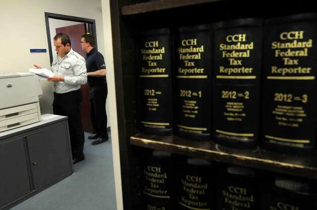 CPA Dave Mahserjian, left, makes copies on Thursday, March 15, 2012, at Teal, Becker & Chiaramonte in Albany, N.Y. The firm was voted a top place to work. (Cindy Schultz / Times Union) Photo: Cindy Schultz / 00016771A