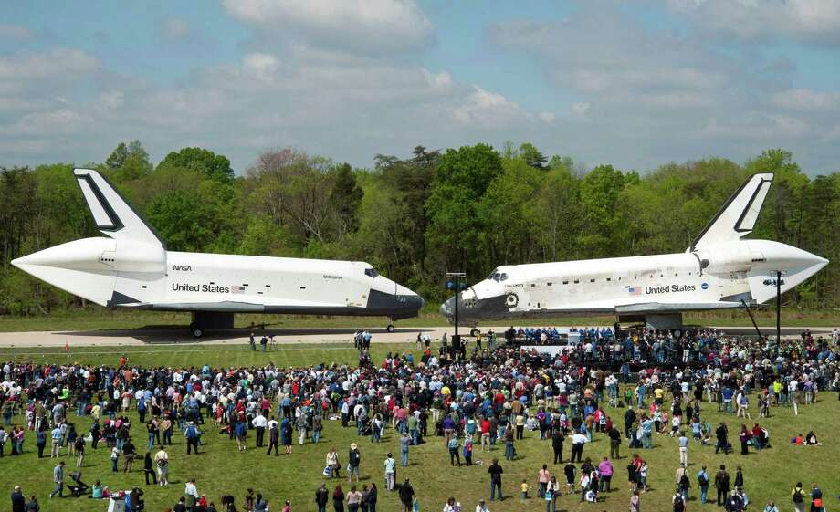 In this photo provided by the Smithsonian Institution via NASA, space shuttles Enterprise, left, and Discovery meet nose-to-nose at the beginning of a transfer ceremony at the Smithsonian's Steven F. Udvar-Hazy Center, Thursday, April 19, 2012, in Chantilly, Va. Space shuttle Discovery will take the place of Enterprise at the center to commemorate past achievements in space and retire as an artifact representing the 30-year shuttle program. (AP Photo/Smithsonian Institution via NASA, Carolyn Russo) Photo: Carolyn Russo, Associated Press / (NASA/Smithsonian Institution/Carolyn Russo)