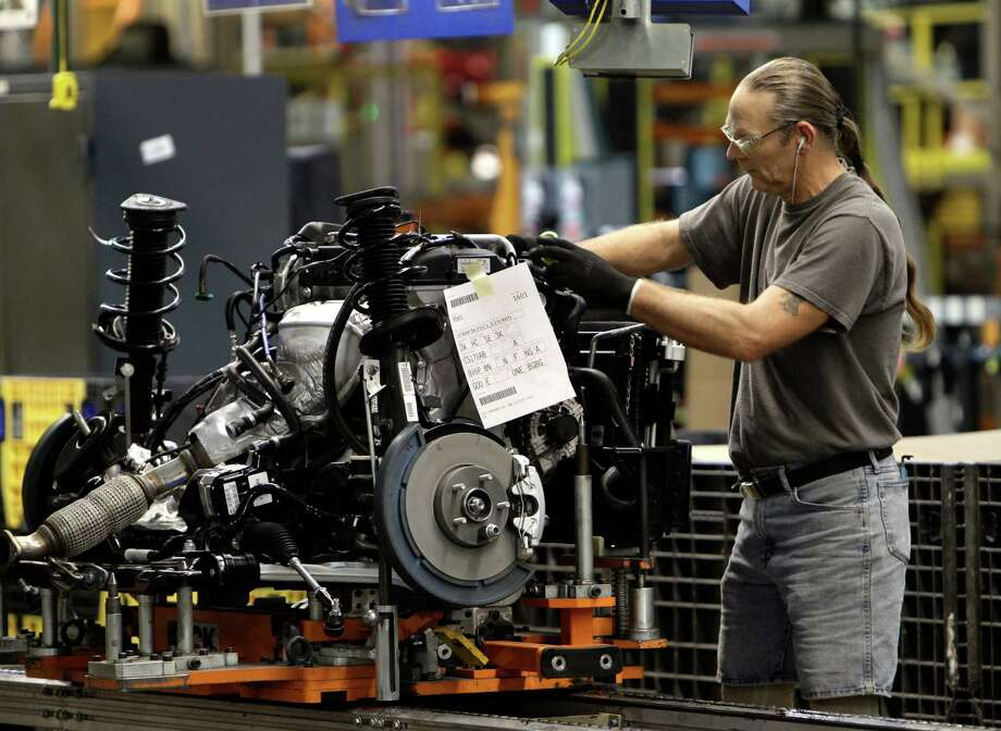 A line worker assembles an engine for a Ford Focus at a plant in Wayne, Mich. Ford is now focusing on smaller, turbocharged engines called EcoBoost. And Ford is even promoting six-cylinder F-150 trucks. Photo: Paul Sancya / AP