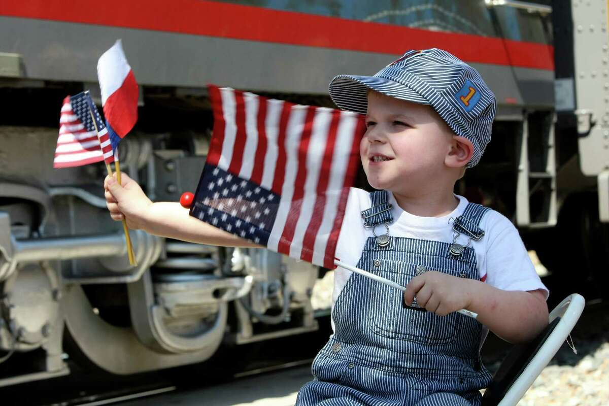 Grady Mueller waves flags as the Union Pacific's vintage E-9 Streamliner diesel locomotive, a sleeker model that took over from the steam engines in the 1950s, leaves the New Braunfels Railroad Museum on Thursday, April 19, 2012.