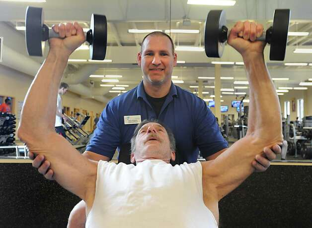 Wellness Center Director John Higgins shows Bill Seltzer of Saratoga Springs the proper form to lift weights at the Saratoga branch YMCA Thursday March 29, 2012 in Saratoga Springs, N.Y. (Lori Van Buren / Times Union) Photo: Lori Van Buren