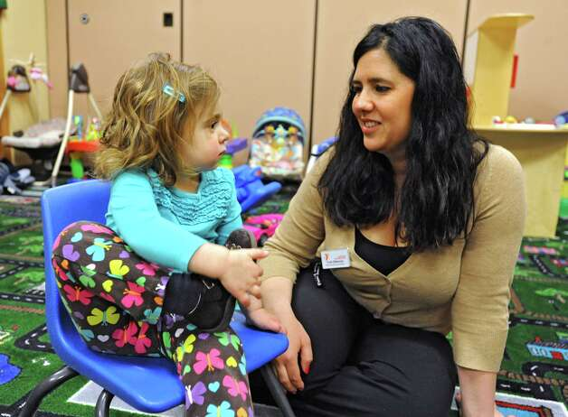 Dorothy Spring, age 2, of Saratoga Springs talks to Trish DiNunzio, babysitting/party coordinator, in the nursery room at the Saratoga branch YMCA Thursday March 29, 2012 in Saratoga Springs, N.Y. (Lori Van Buren / Times Union) Photo: Lori Van Buren