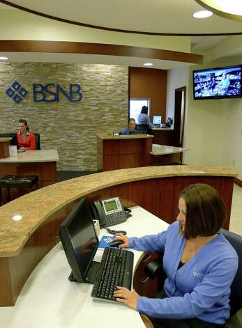 Ballston Spa National Bank sales and service associate Tanya Baker, right, at the bank's headquarters in Ballston Spa N.Y., Thursday March 29, 2012. (Michael P. Farrell/Times Union) Photo: Michael P. Farrell / 00017022A