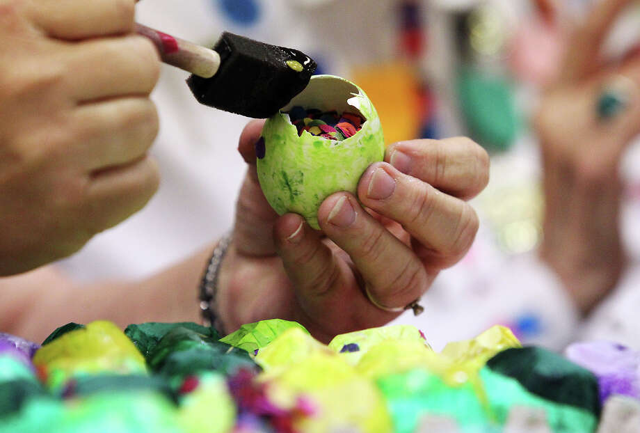 Judy Simon carefully applies glue to a cascarone. Practically year-round, volunteers from the San Antonio Conservation Society spend their time on making cascarones and crepe paper flower decorations for Night in Old San Antonio (NIOSA).  Photo: Kin Man Hui, Kin Man Hui/Express-News / ©2012 San Antonio Express-News