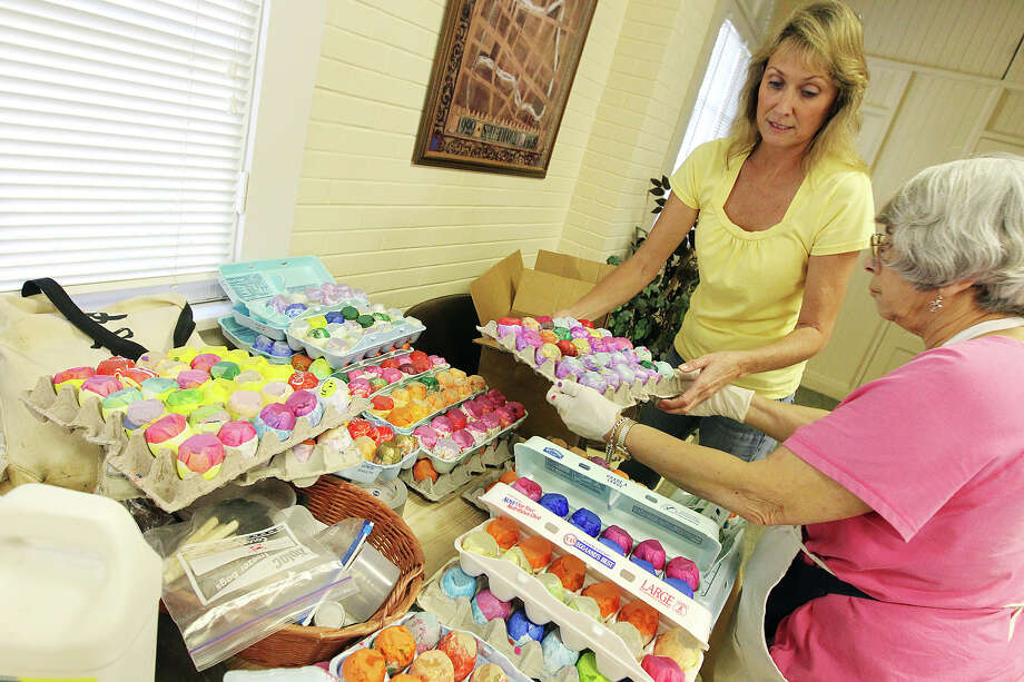 Decoration Chair Elizabeth Schleigh (left) accepts a batch of cascarones from another volunteer on Thursday, Apr. 19, 2012. Practically year-round, volunteers from the San Antonio Conservation Society spend their time on making cascarones and crepe paper flower decorations for Night in Old San Antonio (NIOSA). On Thursday, Apr. 19, 2012, a group of volunteers arrived at Steves Homestead in King William to finish the last batches of cascarones and flowers for the start of the 2012 Fiesta season. Around 75 volunteers collectively made nearly 200,000 cascarones and over 12,000 paper flowers. The eggs are sold at NIOSA with proceeds going to the Conservation Society and their mission of historic preservation. The group which consists mostly women enjoyed chatting and shared a brunch while while they worked on the eggs and flowers. Kin Man Hui/Express-News. Photo: Kin Man Hui, Kin Man Hui/Express-News / ©2012 San Antonio Express-News