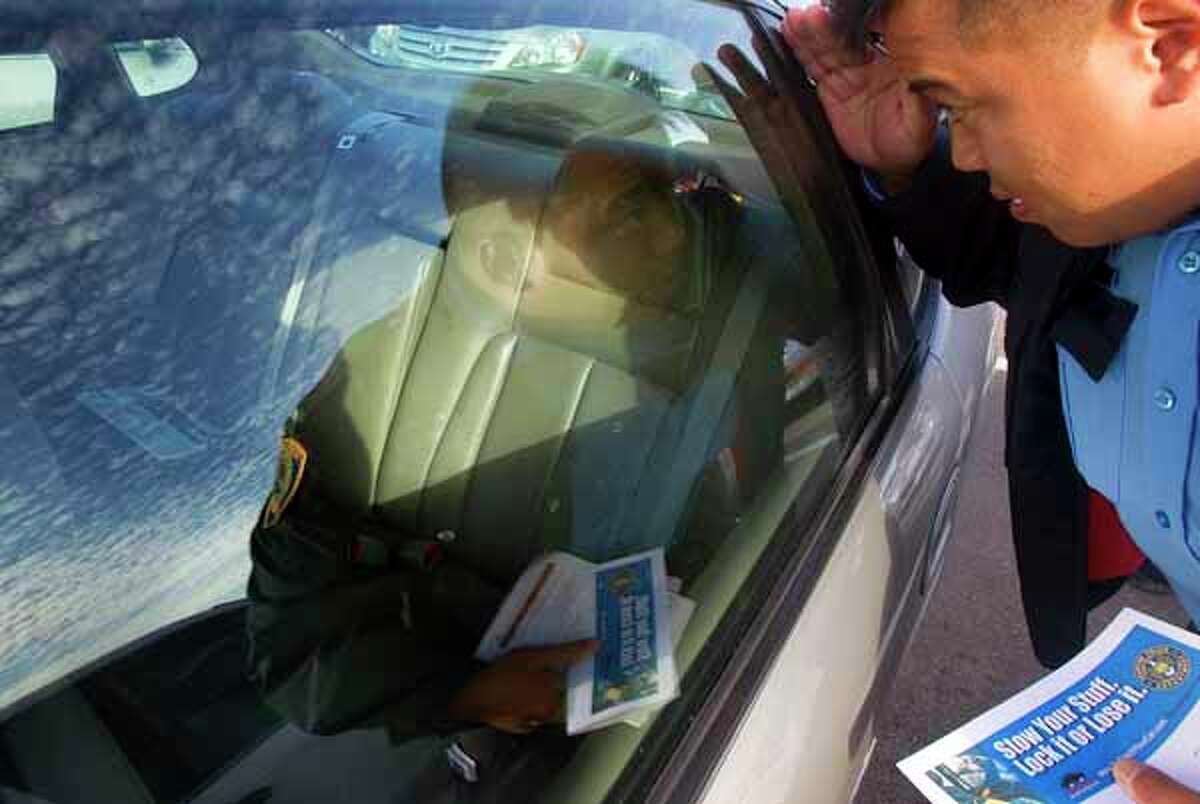 Houston Police Officer P. Ho, checks a car before filling out a Theft Reduction Report Card outside of Randalls Thursday, Dec. 8, 2011, in Houston. HPD joined with the Greater Houston Loss Prevention Alliance made up of retailers in the area, to educate shoppers through the