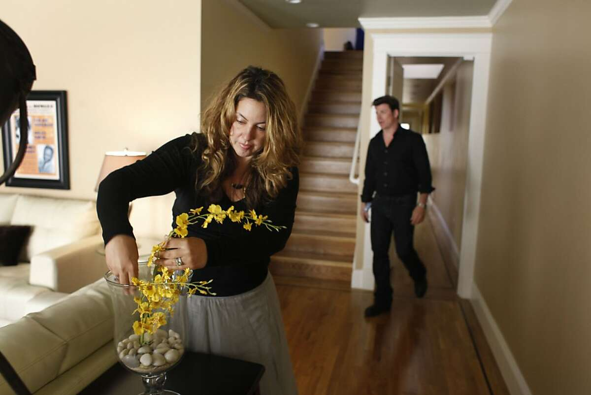 Renee (l to r) and Wyatt Sullivan, owners of Bella Casa Home Staging, make adjustments in a home that was staged by Bella Casa Home Staging on Thursday, April 19, 2012 in San Francisco, Calif.