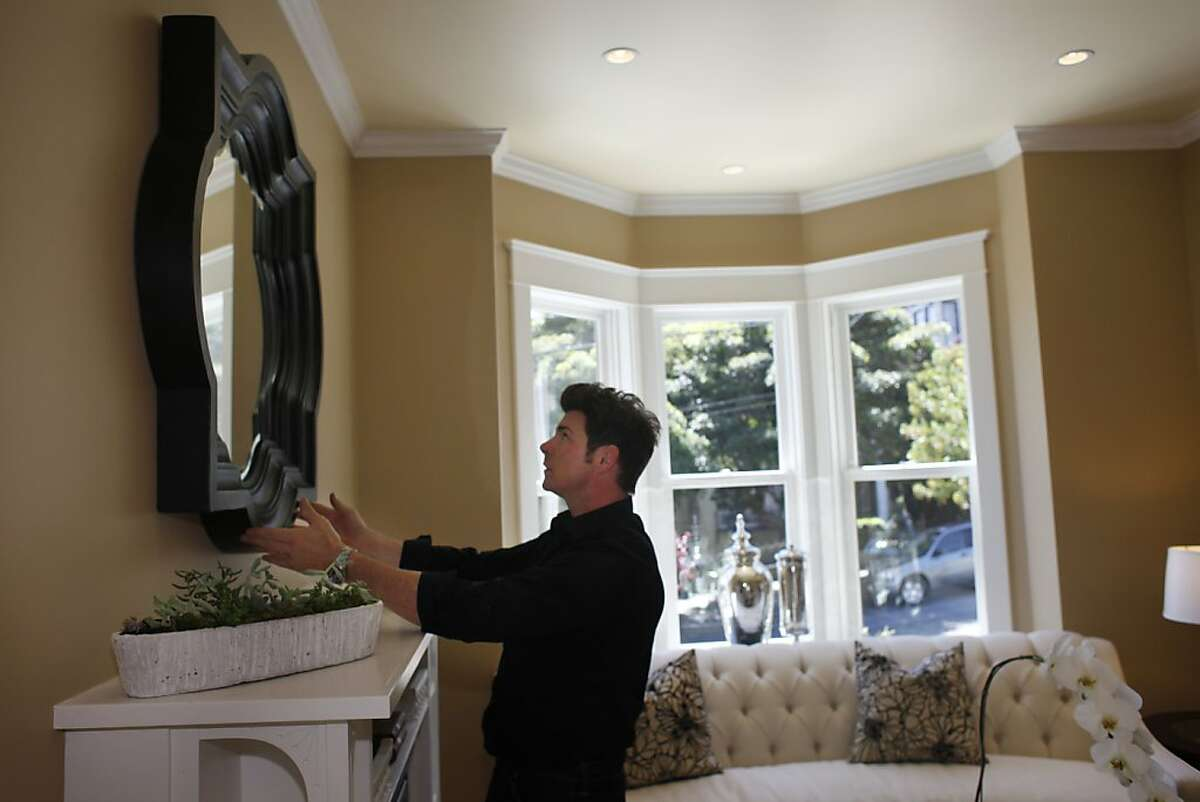 Wyatt Sullivan, co-owner of Bella Casa Home Staging, adjusts a mirror in a living room at a home staged by Bella Casa Home Staging on Thursday, April 19, 2012 in San Francisco, Calif.