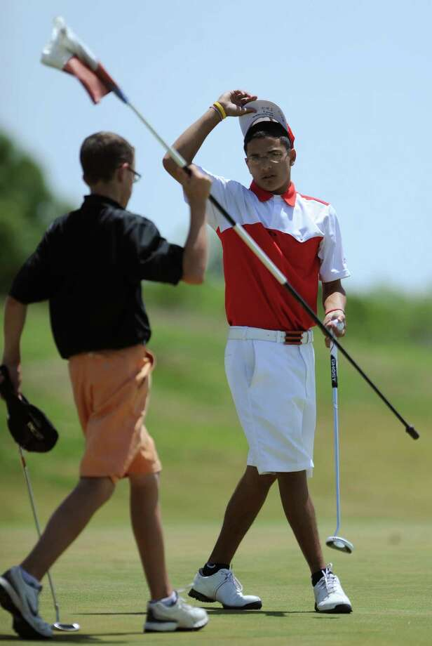 Jason Iozzi, left, of Medina Valley, and Marcus Flores of Corpus Christi Ray finish their round during the Region IV-4A boys golf championship at the Golf Club of Texas on Thursday, April 19, 2012. Photo: BILLY CALZADA, San Antonio Express-News / SAN ANTONIO EXPRESS-NEWS