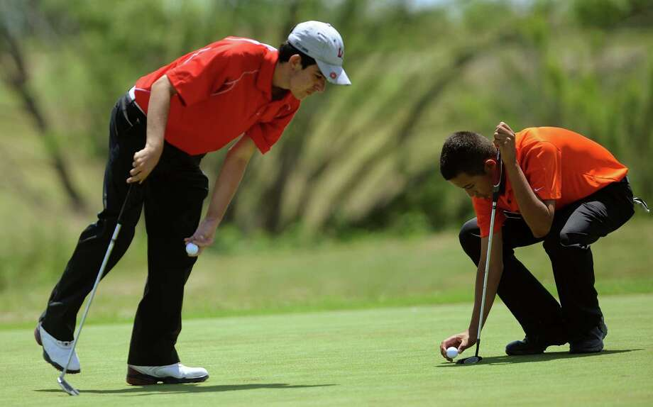 Andrew DeHennis, left, of Austin Lake Travis, and Gary Natal of New Braunfels Canyon examine the 17th green as they prepare to putt during the Region IV-4A boys golf championship at the Golf Club of Texas on Thursday, April 19, 2012. Photo: BILLY CALZADA, San Antonio Express-News / SAN ANTONIO EXPRESS-NEWS